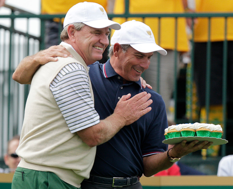 . International team captain Nick Price, left, presents United States team captain Fred Couples with cupcakes for his birthday before the start of the four-ball match at the Presidents Cup golf tournament at Muirfield Village Golf Club Thursday, Oct. 3, 2013, in Dublin, Ohio. (AP Photo/Jay LaPrete)