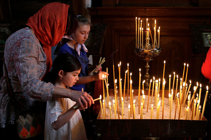 . Russian Christian Orthodox worshippers light a candle after a holy Easter service at the Church of St. Peter and Paul in Karlovy Vary May 5, 2013. The spa town of Karlovy Vary has a large number of Russian residents and is also a popular tourist destination for visitors from Russia.  REUTERS/David W Cerny