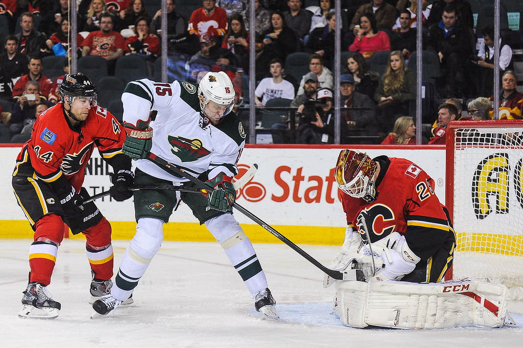 . Reto Berra #29 of the Calgary Flames holds the puck as Dany Heatley #15 of the Minnesota Wild hacks at him during an NHL game at Scotiabank Saddledome on February 1, 2014 in Calgary, Alberta, Canada. (Photo by Derek Leung/Getty Images)