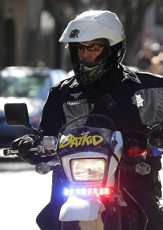 ". A San Francisco Police Officer with a Batkid sign on his bike waits for the arrival of Miles Scott, dressed as Batkid, in San Francisco, Friday, Nov. 15, 2013. San Francisco turned into Gotham City on Friday, as city officials helped fulfill Scott\'s wish to be ""Batkid.\"" Scott, a leukemia patient from Tulelake in far Northern California, was called into service on Friday morning by San Francisco Police Chief Greg Suhr to help fight crime, The Greater Bay Area Make-A-Wish Foundation says. (AP Photo/Jeff Chiu)"
