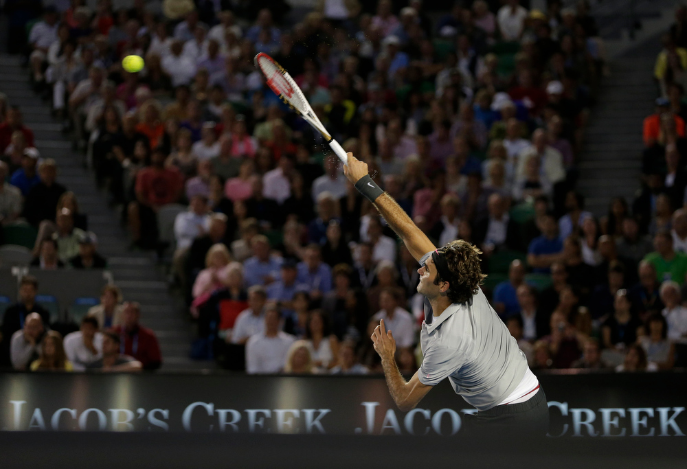 Description of . Switzerland's Roger Federer serves to Britain's Andy Murray during their semifinal match at the Australian Open tennis championship in Melbourne, Australia, Friday, Jan. 25, 2013.   (AP Photo/Andy Wong)