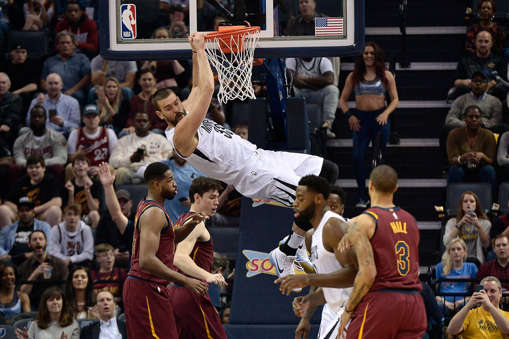 . Memphis Grizzlies center Marc Gasol (33) hangs from the rim after dunking during the first half of the team\'s NBA basketball game against the Cleveland Cavaliers on Friday, Feb. 23, 2018, in Memphis, Tenn. (AP Photo/Brandon Dill)