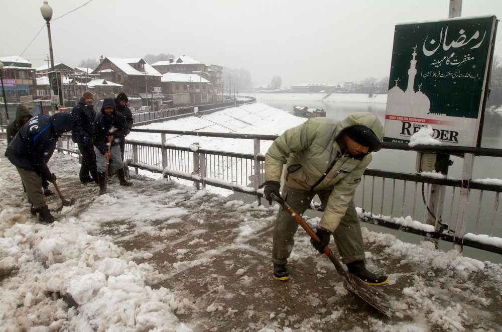 . Kashmiri Muslim men employed by government clear snow from a bridge as it snows in Srinagar, India, Friday, Jan. 18, 2013. Traffic on the 300 kilometers (186 miles) long Jammu-Srinagar national highway was suspended due to heavy snowfall, according to news reports. (AP Photo/Dar Yasin)