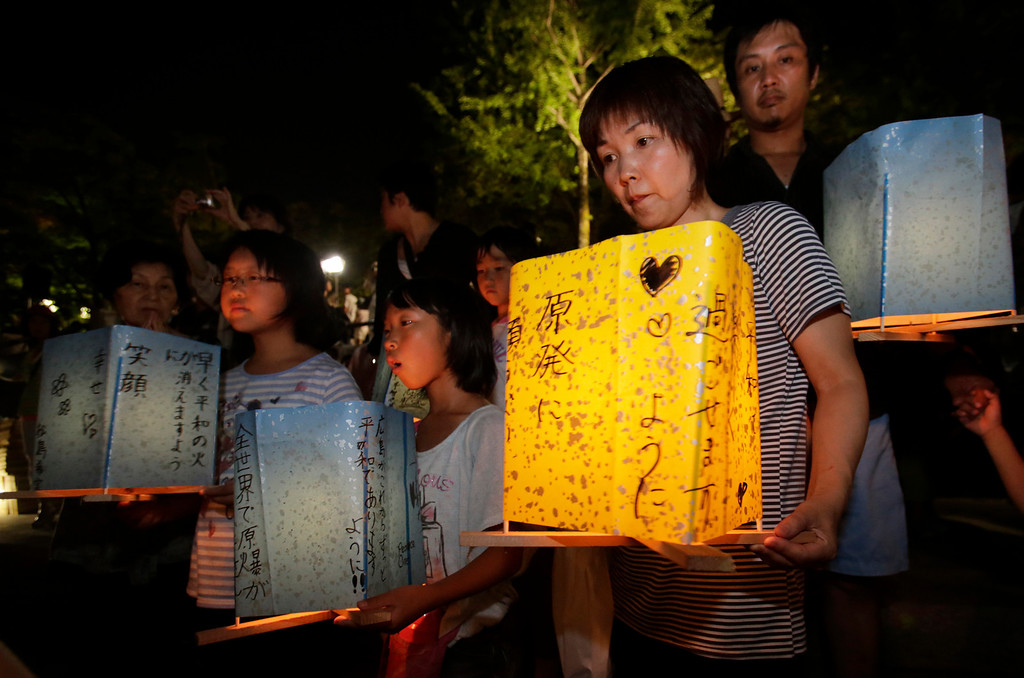 . Residents of Hiroshima hold paper lanterns before releasing them into the Motoyasu River, wishing for the world peace in front of the Atomic Bomb Dome in Hiroshima, western Japan, Tuesday, Aug. 6, 2013.  (AP Photo/Shizuo Kambayashi)