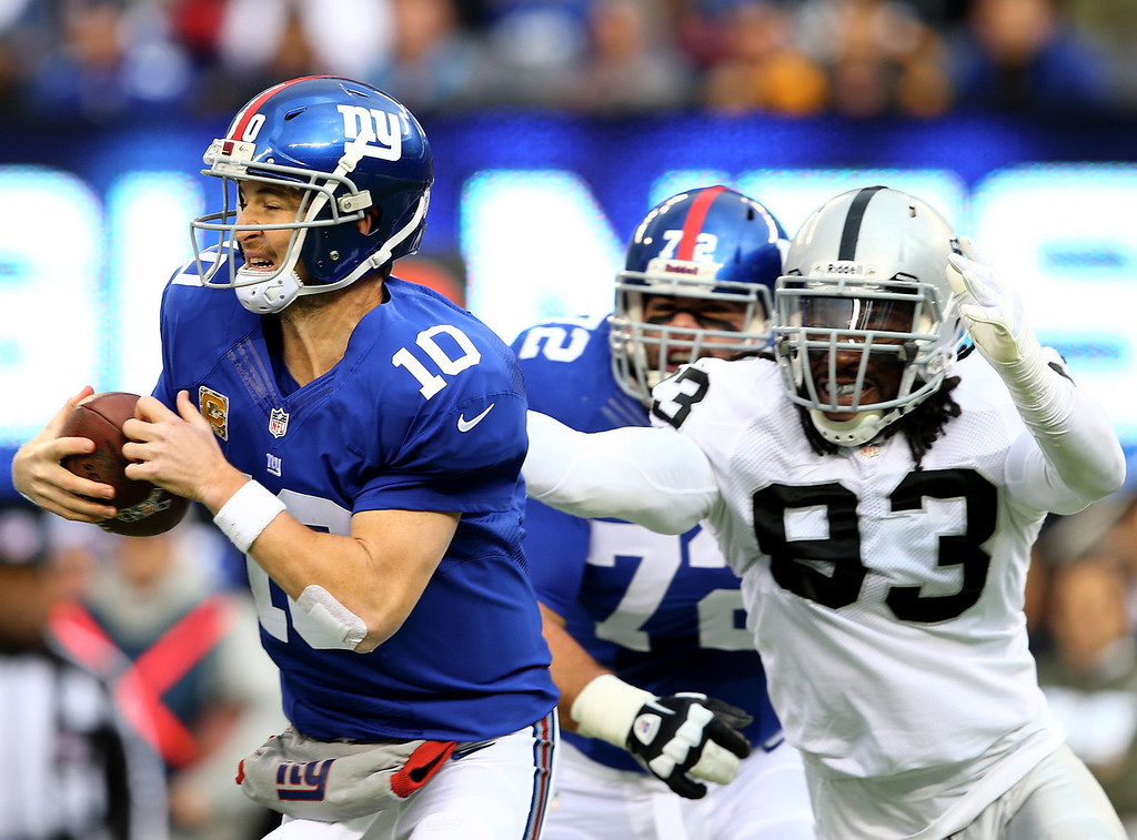 . Eli Manning #10 of the New York Giants is pressured by Jason Hunter #93 of the Oakland Raiders at MetLife Stadium on November 10, 2013 in East Rutherford, New Jersey.  (Photo by Elsa/Getty Images)