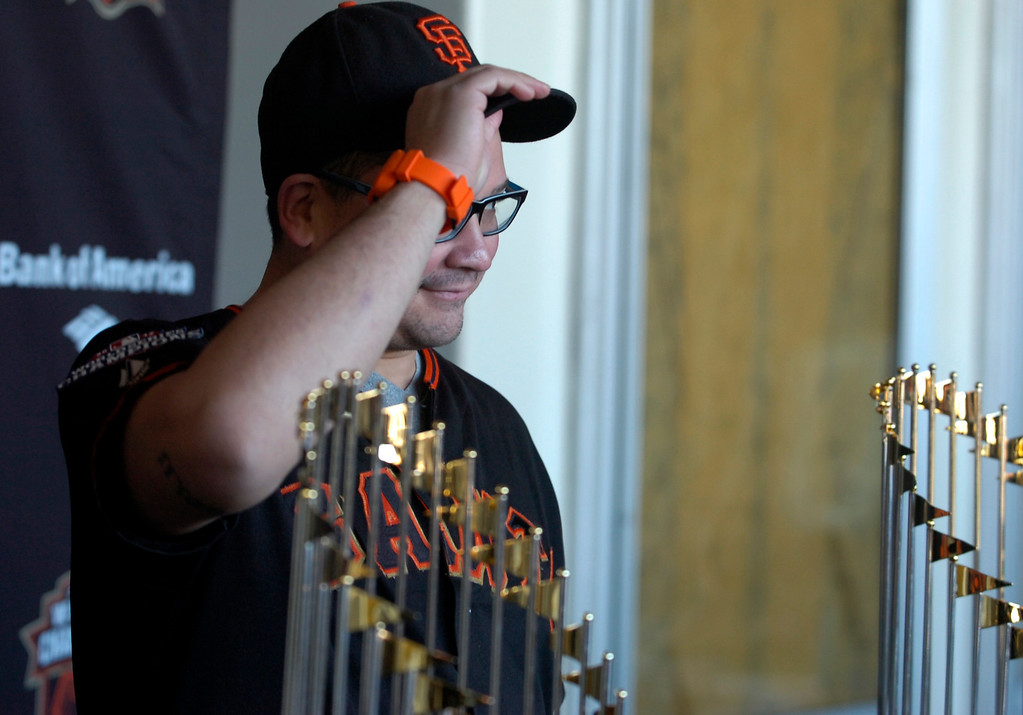 . Vincent LaForm, of Sacramento, adjusts his cap before being photographed with the World Series Trophy as it makes a stop at the Richmond Memorial Auditorium in Richmond, Calif. on Monday, Jan. 14, 2013.  (Kristopher Skinner/Staff)