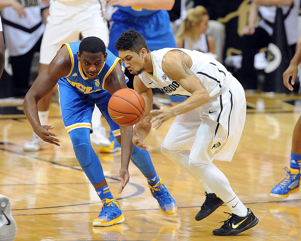 . Askia Booker of CU keeps the ball from Jordan Adams of UCLA during the first half of the January 16, 2014 game in Boulder.  (Cliff Grassmick/Daily Camera)