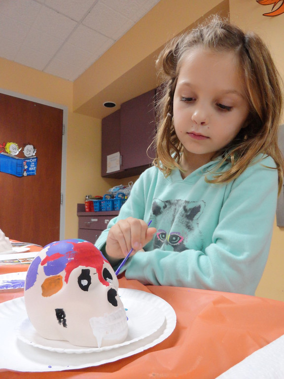 . Ella Mitchell adds a splash of purple to her brightly colored skull during Studio MPL at Mentor Public Library. (Courtesy Mentor Public Library)
