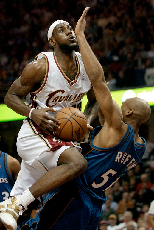 . Jeff Forman/JForman@News-Herald.com LeBron James drives against Michael Ruffin Saturday during the Cavs\' first round game one playoff win over the Wizards.