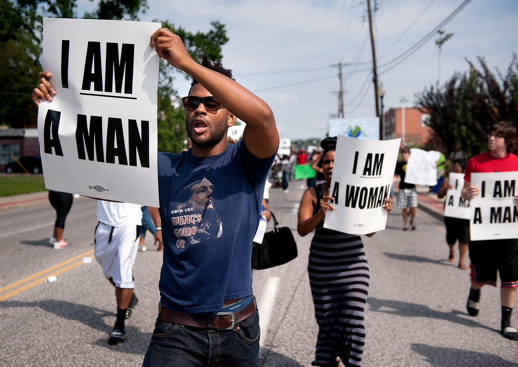 . Aaron Coleman, left, joins other protesters marching on Florissant Road in historic downtown Ferguson, Mo., Monday, Aug. 11, 2014. The group marched along the closed street, rallying in front of the town\'s police headquarters to protest the shooting of 18-year-old Michael Brown by Ferguson police officers. Brown, who was killed in a confrontation with police in the St. Louis suburb, was shot Saturday, Aug. 9, 2014, and died following the confrontation with police. (AP Photo/Sid Hastings)