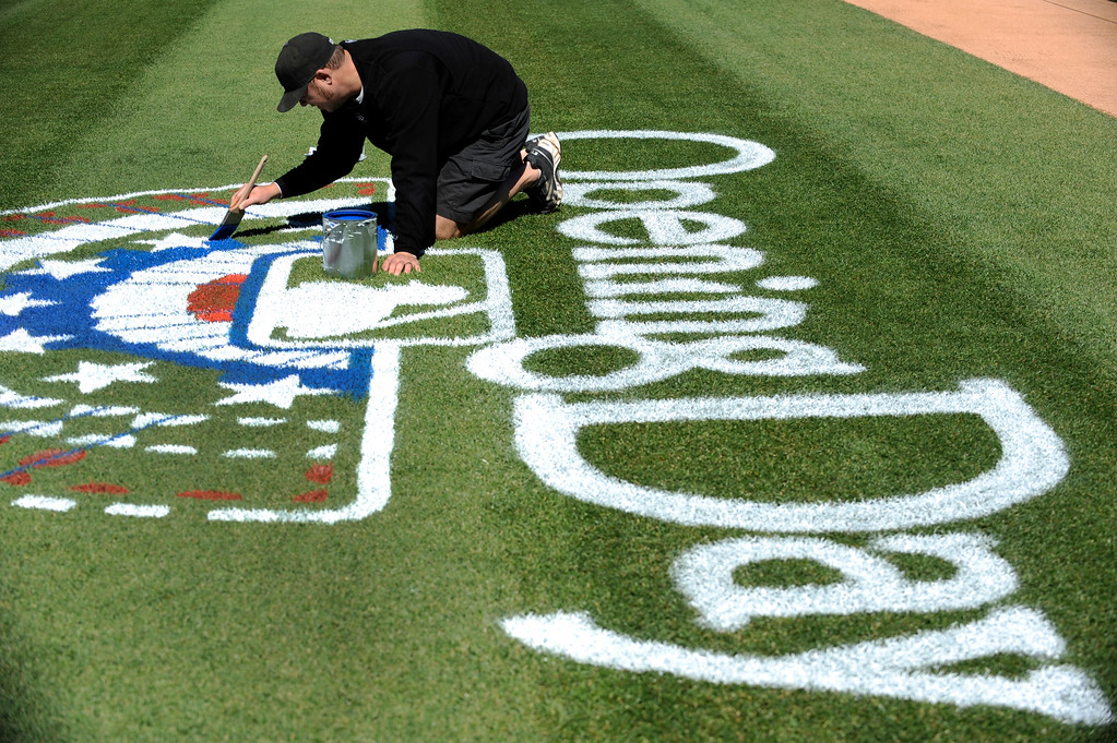 . Jason Garner groundskeeping assistant starts the painting of the Opening Day logo at Coors Field. Colorado Rockies groundkeepers start the tedious work of painting the Opening Day Logo on the field at Coors Field. The Rockies will open the season Friday, April 1, 2011 against the Arizona DiamondBacks. John Leyba, The Denver Post