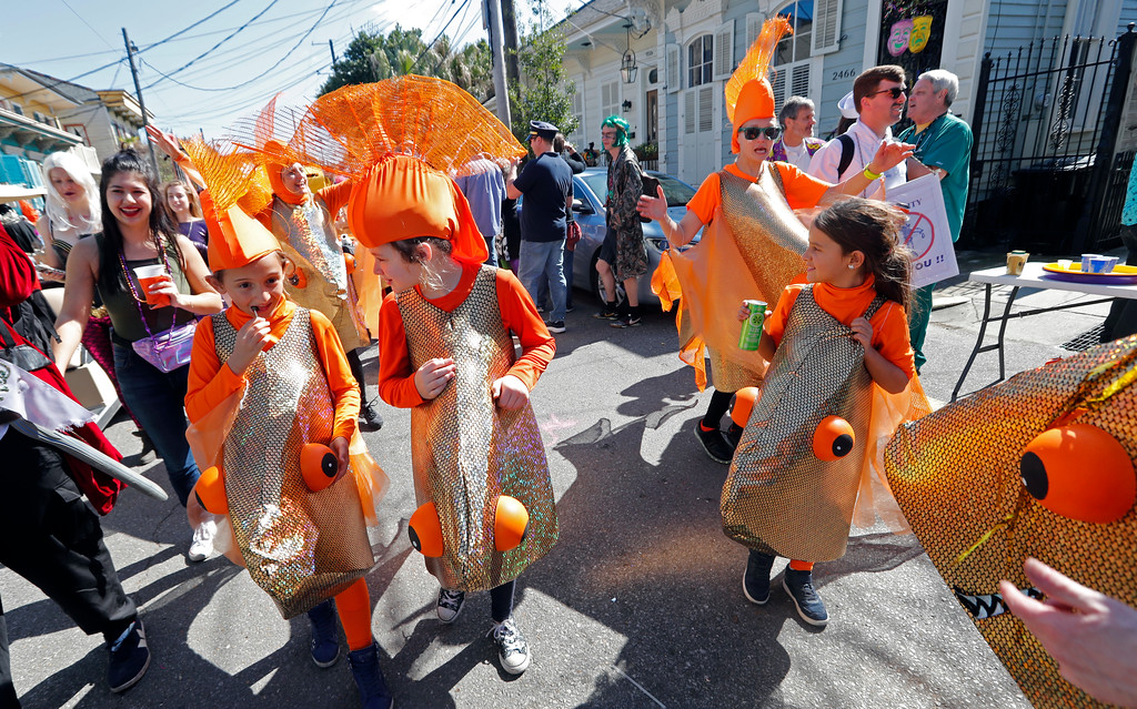 . Children dressed as goldfish walk in the Society de Sainte Anne parade, on Mardi Gras day in New Orleans, Tuesday, Feb. 13, 2018. (AP Photo/Gerald Herbert)