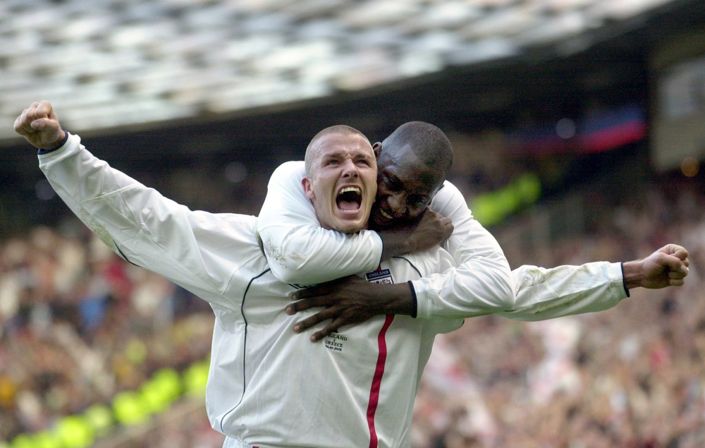 . This is a Saturday, Oct. 6, 2001 file photo of England\'s captain David Beckham, left, as he  is congratulated by teammate Emile Heskey after scoring their second goal against Greece during their 2002 World Cup qualifying match at Old Trafford Manchester England. (AP Photo/Adam Butler, File)