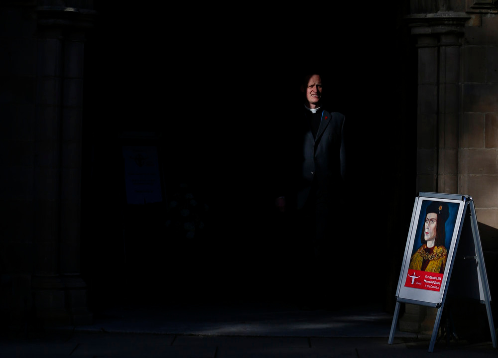 . A member of the clergy walks past a picture of King Richard III at Leicester Cathedral, central England, February 4, 2013. A skeleton with a cleaved skull and a curved spine entombed under a car park is that of Richard III, scientific tests confirmed, solving a 500-year-old mystery about the final resting place of the last English king to die in battle. His bones will be buried at Leicester Cathedral next year. REUTERS/Darren Staples