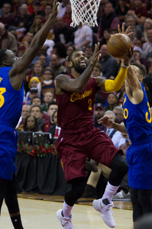 . Kyrie Irving of the Cleveland Cavaliers goes up gor the lay up against Golden State Warrior defenders during an NBA game at the Quicken Loans Arena on Christmas day.  The Cavs defeated the Warriors 109-108.  Michael Johnson - The News Herald