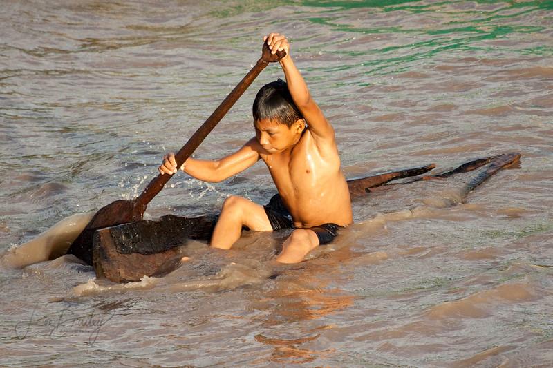 Chipibo boy learning to row in a broken peka-peka boat