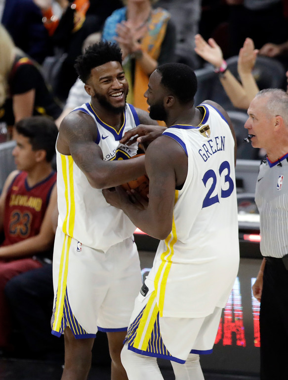 . Golden State Warriors\' Draymond Green (23) and Jordan Bell celebrate following Game 4 of basketball\'s NBA Finals against the Cleveland Cavaliers, Friday, June 8, 2018, in Cleveland. The Warriors defeated the Cavaliers 108-85 and swept the series. (AP Photo/Tony Dejak)