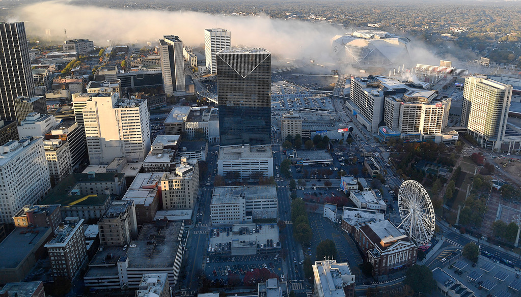 . Smoke moves over downtown Atlanta as the Georgia Dome is destroyed in a scheduled implosion, Monday, Nov. 20, 2017. The dome was not only the former home of the Atlanta Falcons but also the site of two Super Bowls, 1996 Olympics Games events and NCAA basketball tournaments among other major events. (AP Photo/Mike Stewart)