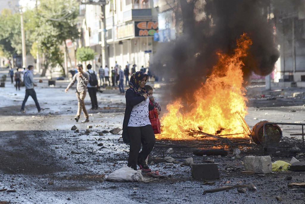 . A woman and a child walk in a street as Kurdish protesters clash with Turkish riot policemen in the southeastern city of Diyarbakir on October 7, 2014 during a demonstration to demand more western intervention against Islamic State militants (IS) in Syria and Iraq. INILYAS AKENGIN/AFP/Getty Images