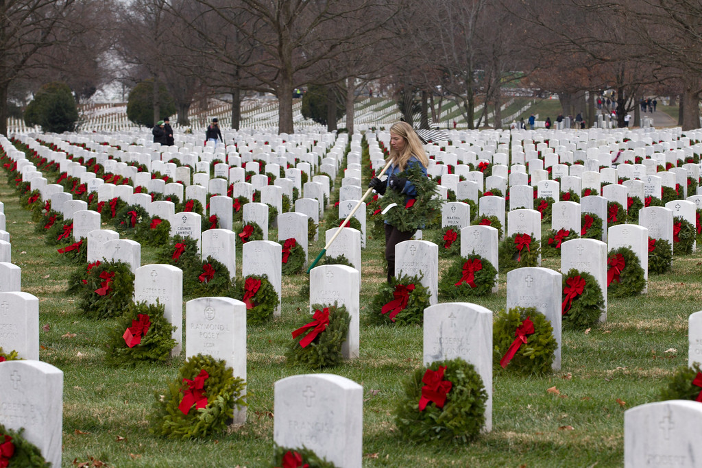. Volunteer Dotti Parker lays holiday wreaths at graves at Arlington National Cemetery in Arlington, Va., Saturday Dec. 14, 2013, during Wreaths Across America Day. Wreaths Across America was started in 1992 at Arlington National Cemetery by Maine businessman Morrill Worcester and has expanded to hundreds of veterans\' cemeteries and other locations in all 50 states and beyond. (AP Photo/Jose Luis Magana)