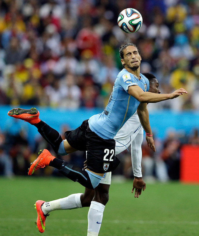 . Uruguay\'s Martin Caceres heads the ball past England\'s Danny Welbeck during the group D World Cup soccer match between Uruguay and England at the Itaquerao Stadium in Sao Paulo, Brazil, Thursday, June 19, 2014.  (AP Photo/Kirsty Wigglesworth)