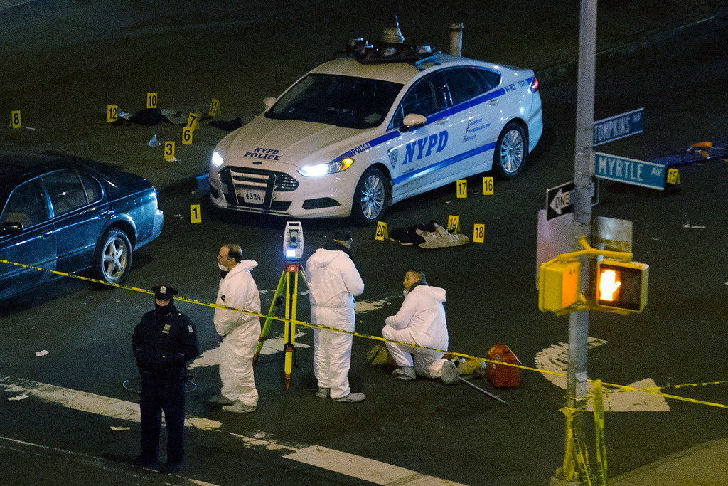. Investigators work at the scene where two NYPD officers were shot, Saturday, Dec. 20, 2014 in the Bedford-Stuyvesant neighborhood of the Brooklyn borough of New York. Police said an armed man walked up to two officers sitting inside the patrol car and opened fire before running into a nearby subway station and committing suicide. Both police officers were killed. (AP Photo/John Minchillo)