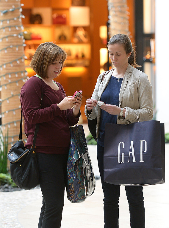 . Nicole Lustig, left, and Melissa Lewis text a friend while shopping at the Westfield Topanga, Thursday, December 26, 2013. Lustig and Lewis make the day after Christmas an annual shopping day. (Photo by Michael Owen Baker/L.A. Daily News)