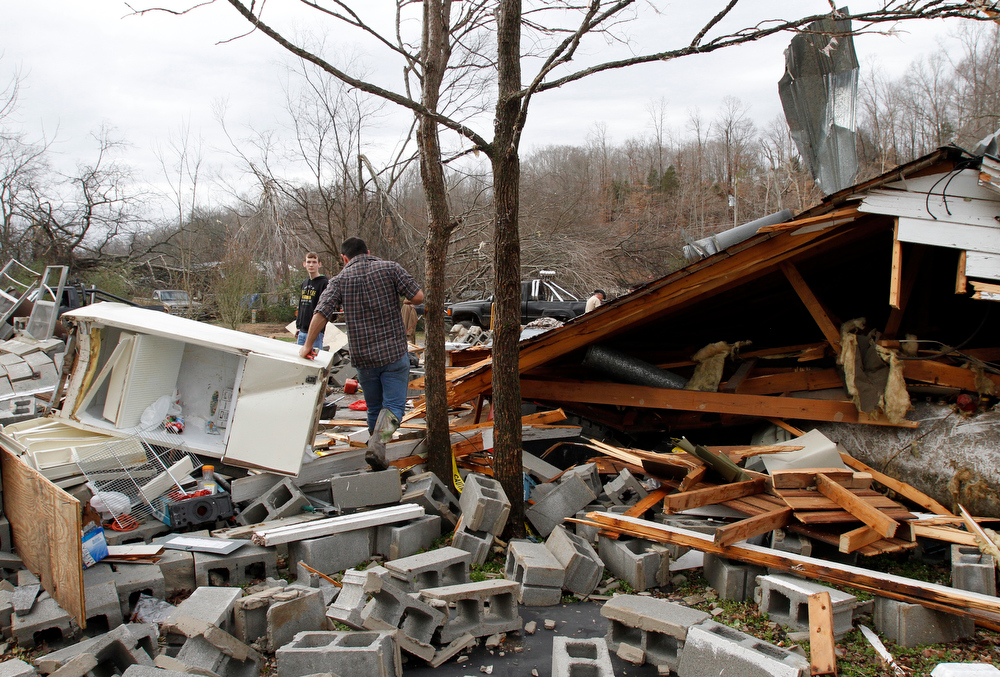 Description of . Residents search through debris after a suspected tornado ripped through early morning destroying several homes and businesses on Wednesday, Jan. 30, 2013, in Coble, Tenn. A massive storm system is raking the Southeast (AP Photo/Butch Dill)