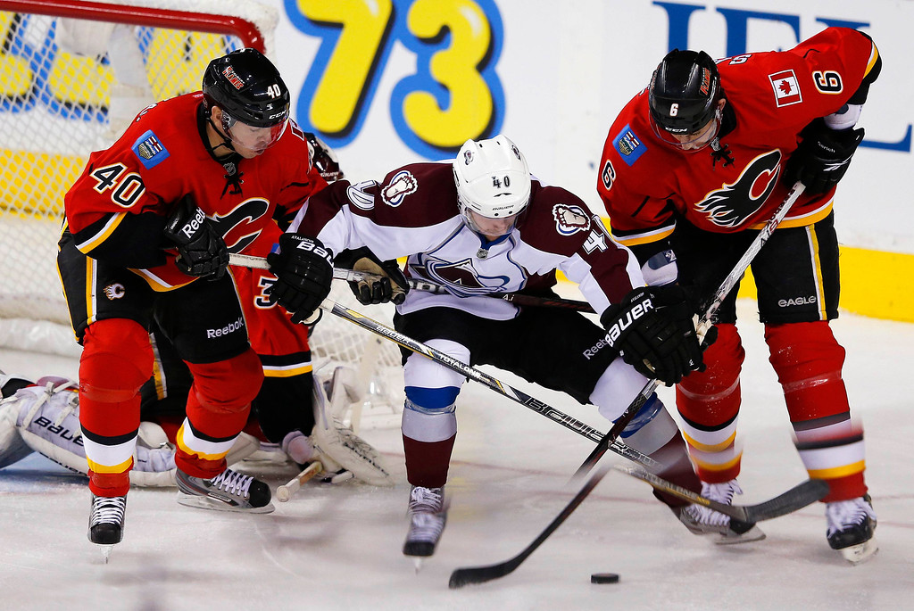. Colorado Avalanche\' Mark Olver (C) battles Calgary Flames\' Alex Tanguay (L) and Cory Sarich for the puck during the first period of their NHL hockey game in Calgary, Alberta, January 31, 2013. REUTERS/Todd Korol
