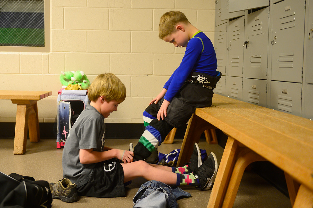 . Jeff Witwer helps to tie his brother\'s, Kit, skates before the start of practice at Edge Ice Arena on February 17, 2016 in Littleton, Colorado. Hockey has developed a following in Colorado especially after the Colorado Avalanche moved into the state 20 years ago. The interest in hockey has begun to boom from three-year-olds to adults, either playing in recreation leagues or learning the game for the first time. The Foothill Flyers are one of those organizations seeing some of that trend with enrollment in their Under 8 league going from 50 children to 100 in three years. (Photo by Brent Lewis/The Denver Post)
