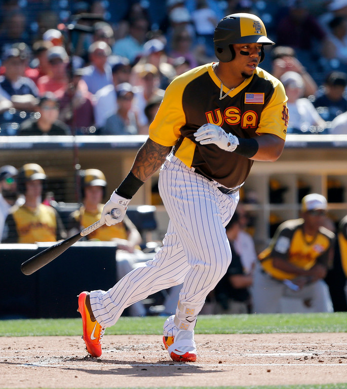 . U.S. Team\'s Dominic Smith, of the New York Mets, follows through on a base hit during the second inning of the All-Star Futures baseball game against the World Team, Sunday, July 10, 2016, in San Diego. (AP Photo/Lenny Ignelzi)