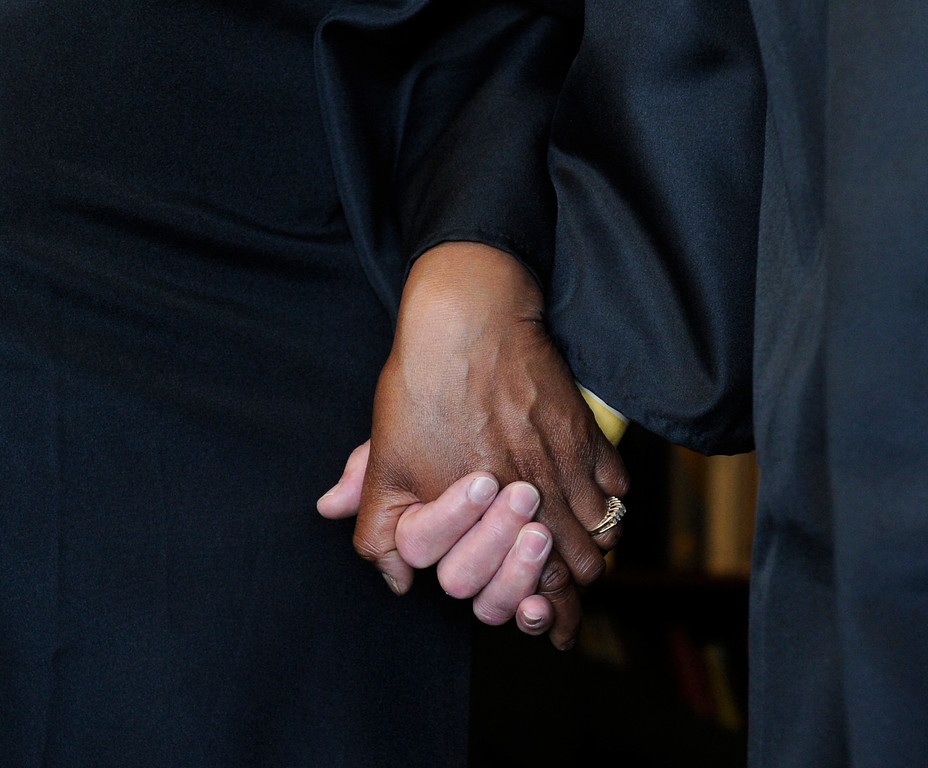 . Fellow graduates hold hands as the group says a prayer before the ceremony. (Photo By Kathryn Scott Osler/The Denver Post)