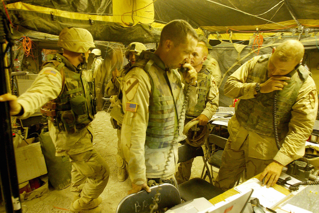 """. US troops from the 2/7 Cavalry discuss the latest military operations at their  \""""operation room\""""  close to the restive Sunni Muslim city of Fallujah10 November 2004. AFP PHOTO/PATRICK BAZ/AFP/Getty Images)"""
