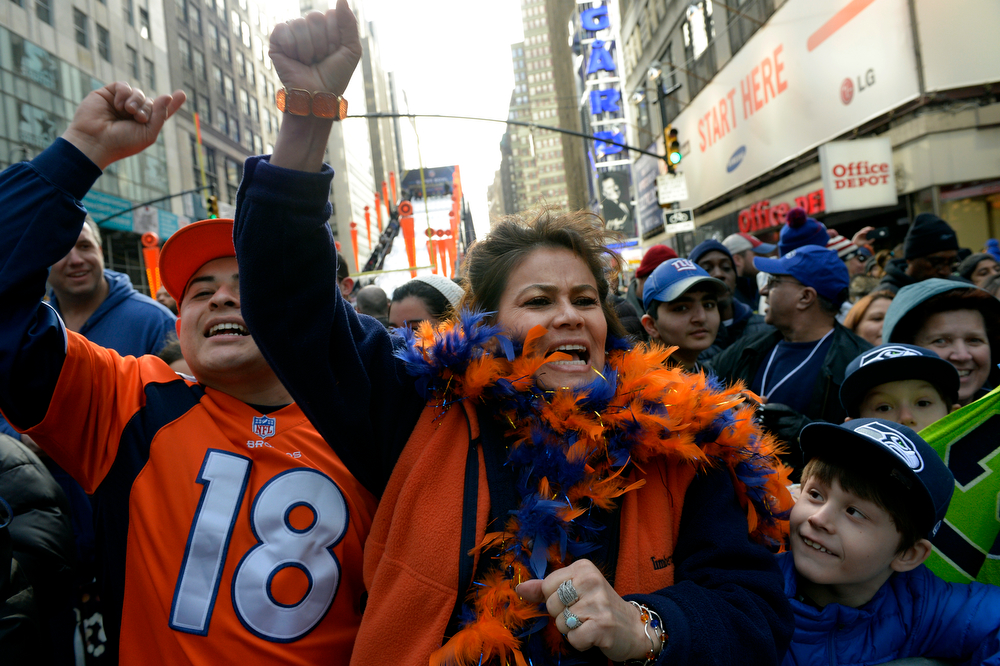 Description of . Broncos fans Tressie Landau, of Aurora, and her son Dominic Carasco cheer for the Broncos while watching the Press Box Tailgating Show on Super Bowl Boulevard in New York, NY February 02, 2014. The NFL has transformed 13 blocks of Broadway into a center for Super Bowl activity before Sundays Super Bowl between the Denver Broncos and Seattle Seahawks. Landau predicted a the Broncos winning by 3 or 6 points. (Photo By Craig F. Walker / The Denver Post)