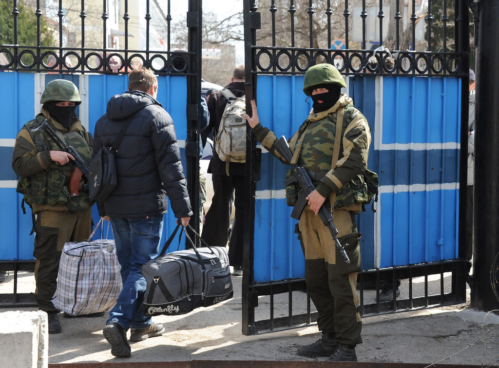 . Ukrainian officers leave as Russian soldiers patrol at the Ukrainian navy headquarters in the Crimean city of Sevastopol on March 19, 2014.   AFP PHOTO/  VIKTOR  DRACHEV/AFP/Getty Images