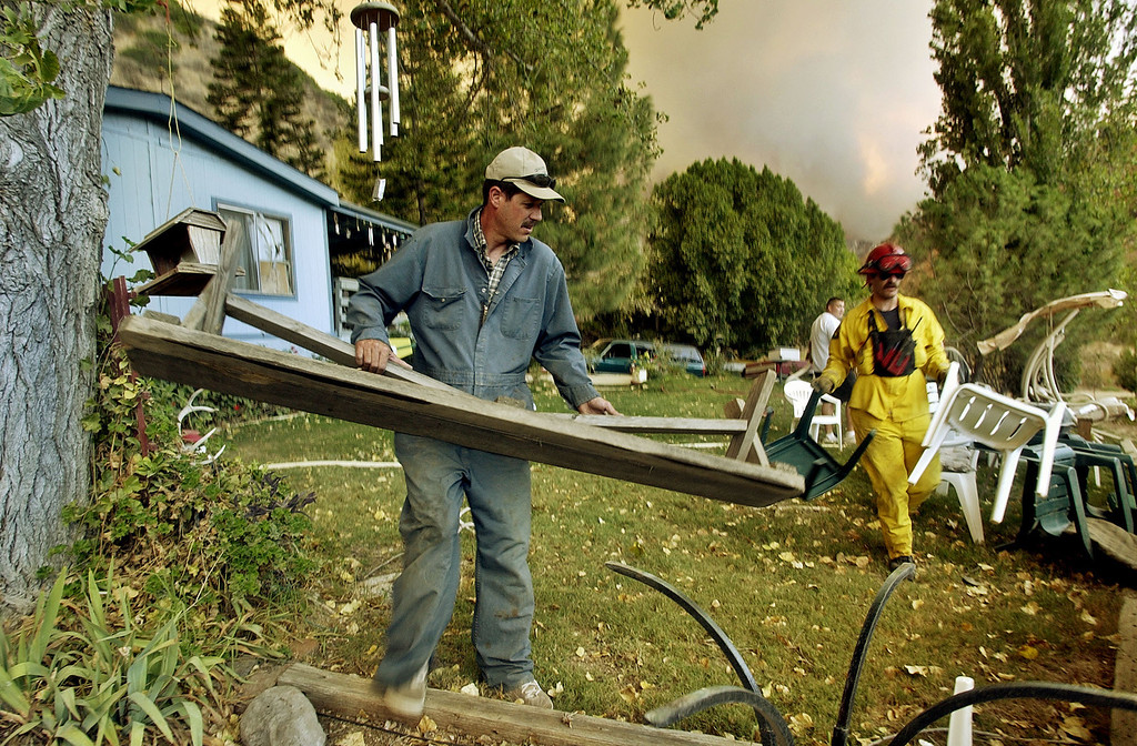 . Family members and Ventura County firefighters move items away from Bob McCary\'s home as a fire above Hopper Canyon threatens the neighborhood of Fillmore, Calif. Sunday afternoon, Oct. 26, 2003.  The fire known as the Piru fire, that had been approcaching containment, flared anew Sunday.  (AP Photo/Reed Saxon)