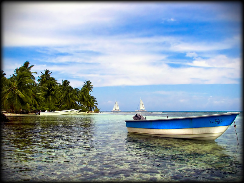 Beautiful photograph of a boat floating in a tropical lagoon / bay / shoreline.