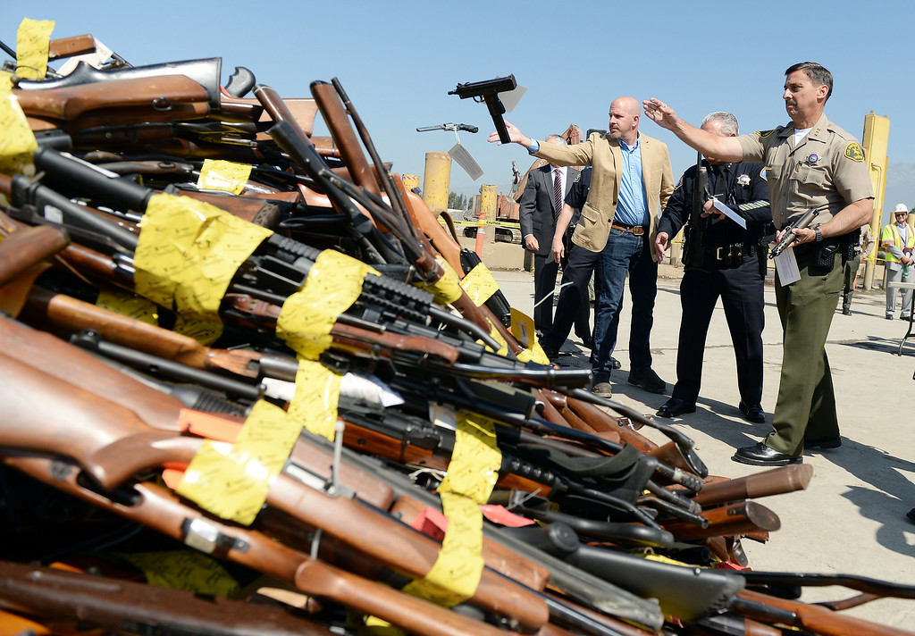 . Los Angeles County Assistant Sheriff Todd Rogers throws a confiscated hand gun into a pile at Gerdau Steel Mill in Rancho Cucamonga Wednesday August 13, 2014. Approximately 4,700 weapons confiscated amongst 12 Los Angeles County law enforcement agencies were melted down into steel.   (Will Lester/Inland Valley Daily Bulletin)