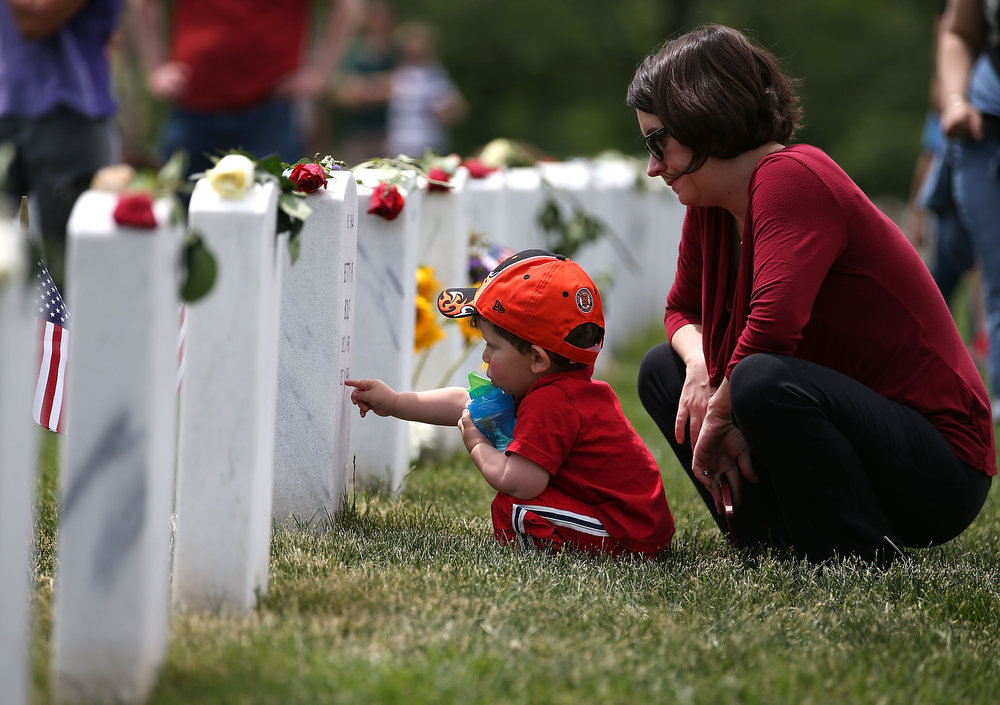 . Anne Kornblut and her two-year-old son visit a gravesite in section 60 at Arlington Cemetery, May 27, 2013 in Arlington, Virginia. For Memorial Day President Obama layed a wreath at the Tomb of the Unknowns, paying tribute to military veterans past and present who have served and sacrificed their lives for their country.  (Photo by Mark Wilson/Getty Images)