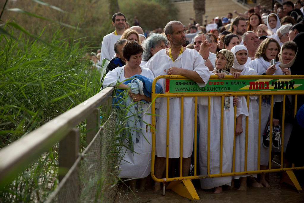 . Christian Orthodox pilgrims wait to be baptized during the traditional Epiphany baptism ceremony at the Qasr-el Yahud baptism site in the Jordan river near the West Bank town of Jericho, Monday, Jan. 18, 2016. The site is traditionally believed by many to be the place where Jesus was baptized. (AP Photo/Ariel Schalit)