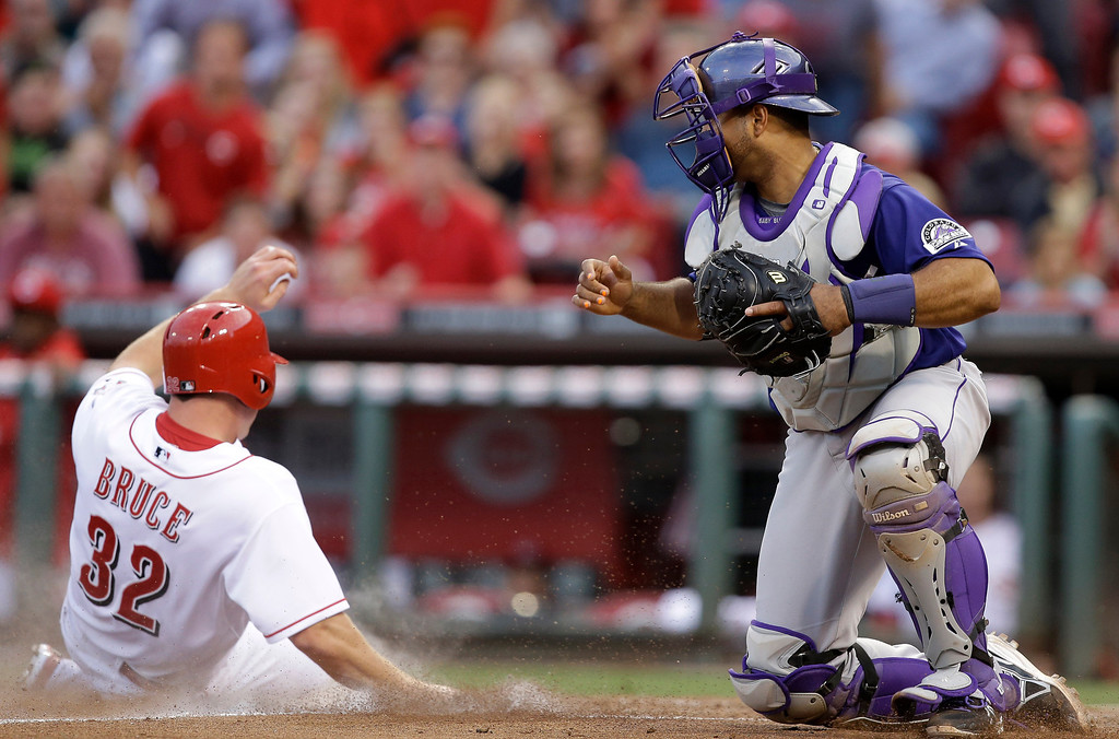 . Cincinnati Reds\' Jay Bruce (32) is safe at home as Colorado Rockies catcher Wilin Rosario is pulled to the right by the throw in the fourth inning of a baseball game, Monday, June 3, 2013, in Cincinnati. (AP Photo/Al Behrman)
