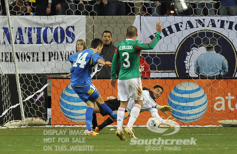 Mexico's Goalkeeper Jesus Corona (#1) makes the save on Bosnia-Herzegovina's Forward Vedad Ibisevic (#14) shot in Soccer action between Bosnia-Herzegovina and Mexico.  Mexico defeated Bosnia-Herzegovina 2-0 in the game at the Georgia Dome in Atlanta, GA.