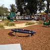 noval spinner and spring rocker in mulch and dry creek bed with grasses and spiral slide