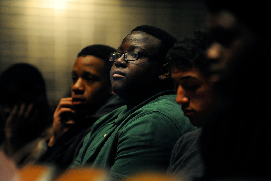 . Lavelle Simmons, center, a sophomore at George Washington High School, listens to a panel of Black Men in Support of Education, a group of successful black men who mentor kids, as they speak on March 26 to students at the high school in Denver, Colo. Photo by Jamie Cotten, Special to The Denver Post