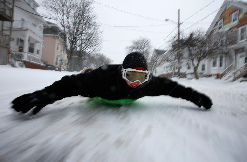 . Gabby DiGiacomo, of Whitefield, Maine, slides down Congress Street in Portland, Maine, on a saucer during the latest winter storm, Tuesday, March 13, 2018, in Portland, Maine. With the exception of snowplows, the streets had very little traffic during the third major nor\'easter in two weeks to slam the storm-battered Northeast. (AP Photo/Robert F. Bukaty)