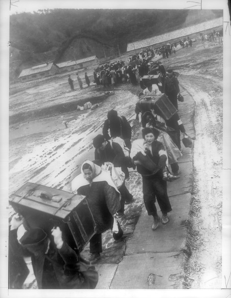 """""""Carrying luggage and babies, long line of repatriates wends way over catwalk, last stage of trip from China where some have been in exile.  Others had never seen homeland.""""--caption on photograph"""