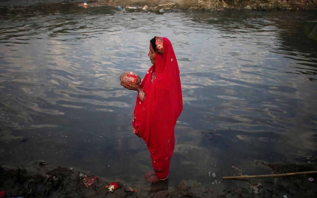 . A Nepalese woman offers prayers in the Bagmati River during Chhath puja festival in Katmandu, Nepal, Monday, Nov. 8, 2013. (AP Photo/Niranjan Shrestha)