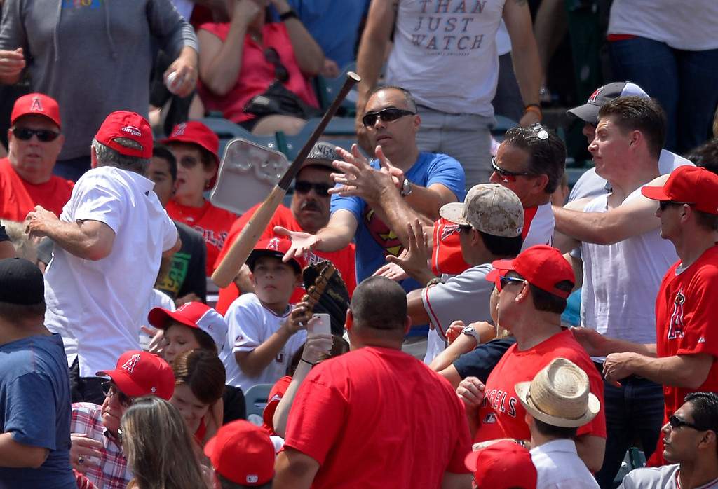 . Fans try to catch a bat that was accidentally thrown by Los Angeles Angels\' Howie Kendrick during the seventh inning of their baseball game against the Pittsburgh Pirates, Sunday, June 23, 2013, in Anaheim, Calif.  (AP Photo/Mark J. Terrill)