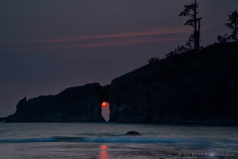 The sun sets right behind the natural arch at Second Beach - La Push, WA