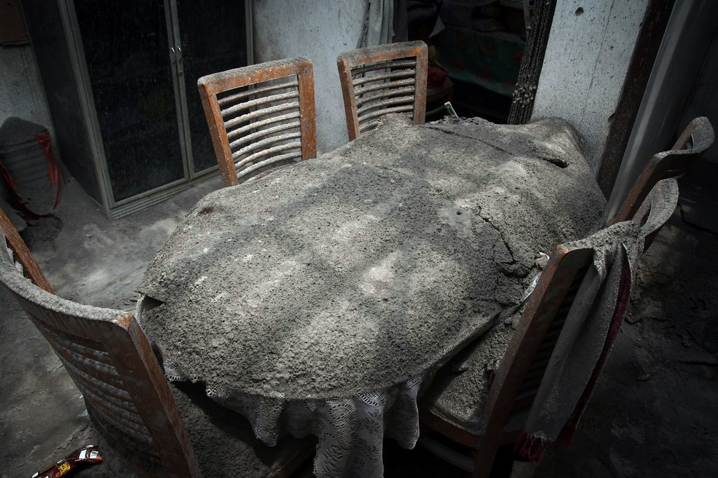. A dining table is covered by ash inside a house damaged by heavy ashfall in Malang, East Java on February 16, 2014 following the volcanic eruption of Mount Kelud in East Java on February 13. T AFP PHOTO / Aman ROCHMAN/AFP/Getty Images